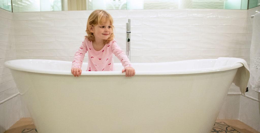 Toddler standing in huge bathtub
