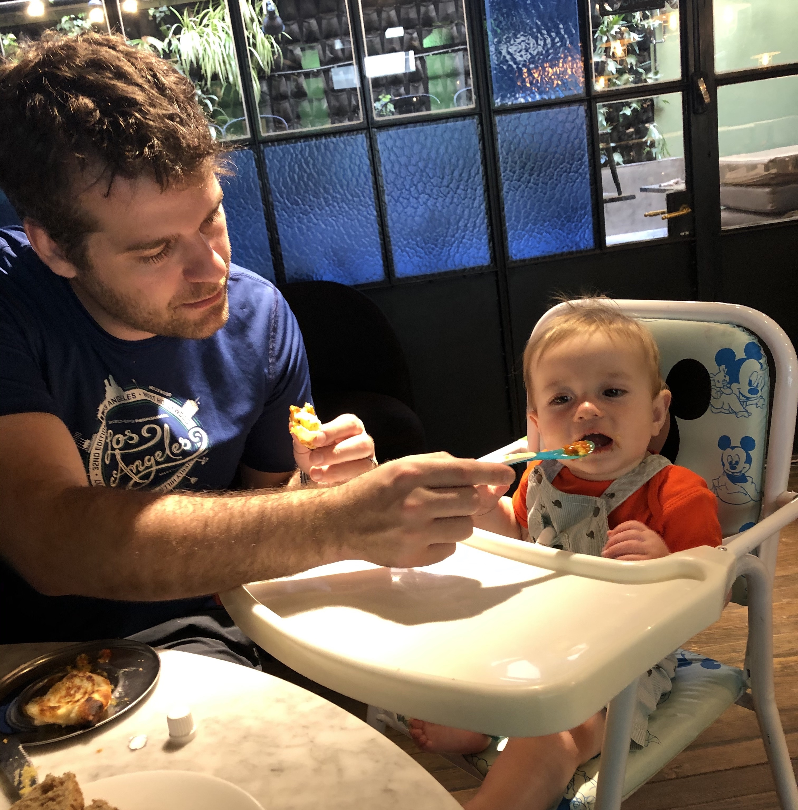 Father feeding baby empanadas in Buenos Aires, Argentina | getting your baby to sleep through the night