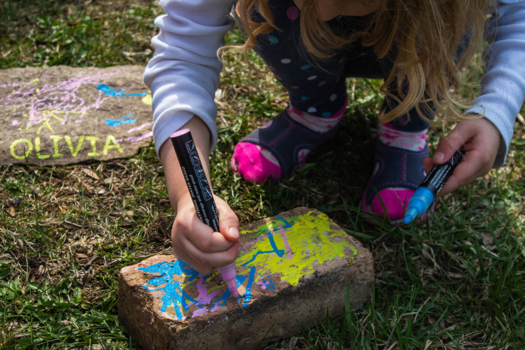 Toddler painting rocks outside