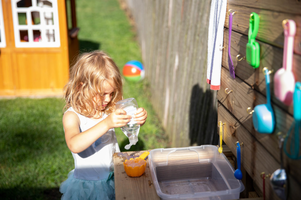 4 year old girl washes dishes with soap in her DIY mud kitchen