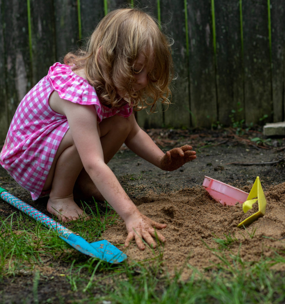 4 year old digs in the dirt with beach toys