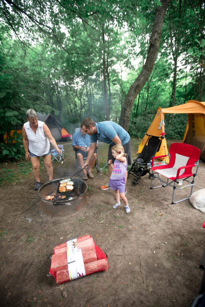 family cooking lunch together during a tent camping trip in Wisconsin