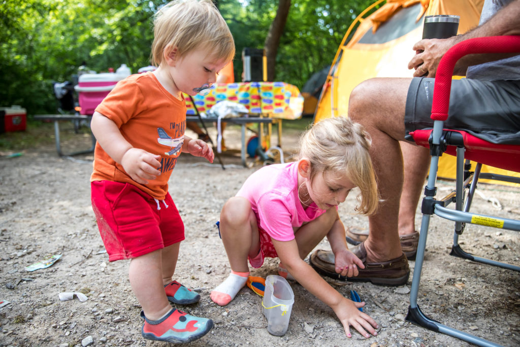 4-year old teaches 1-year old about bug hunting while on a camping trip