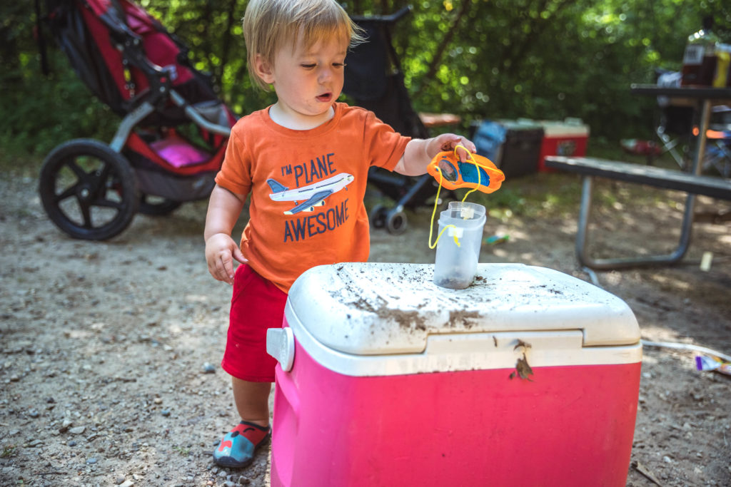 1-year old using a bug catcher while camping