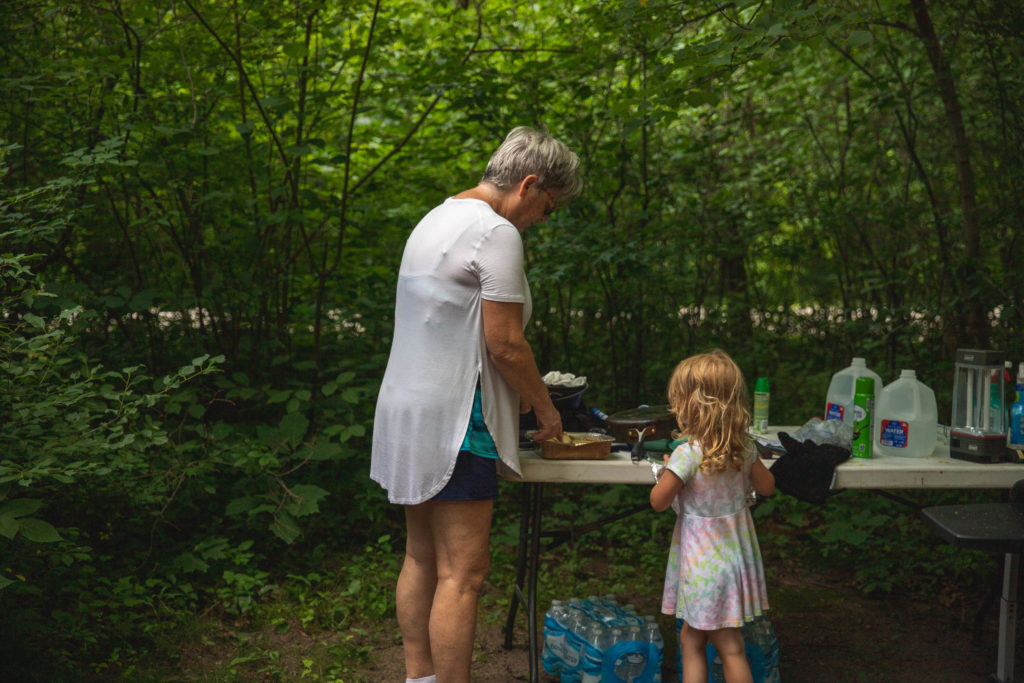 4-year old helping grandma cook breakfast during a camping trip