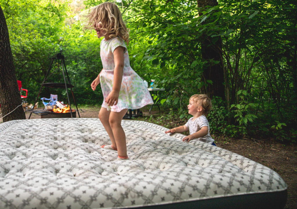 Young kids dancing and jumping on an air mattress during a camping trip | camping activities with kids