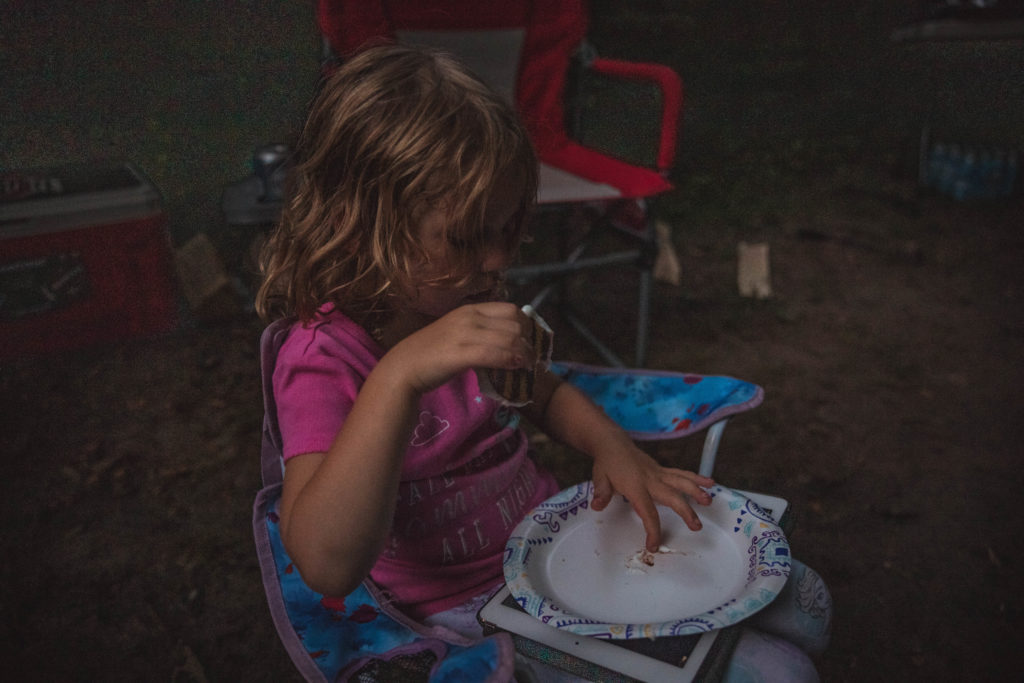 4 year old girl eats a cookie smore while tent camping | camping activities with kids