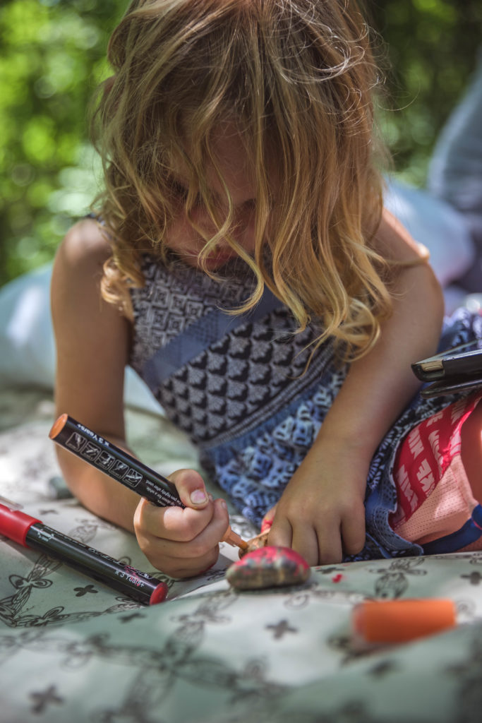 4-year old painting rocks during a camping trip