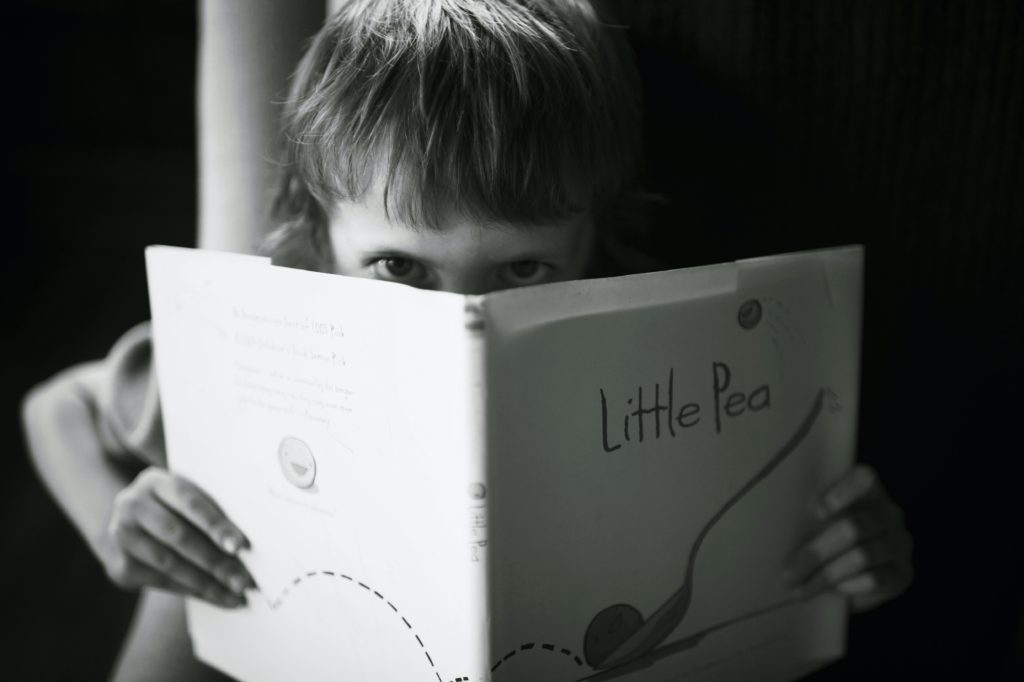 Young kid peeking over a book | how to stop a temper tantrum