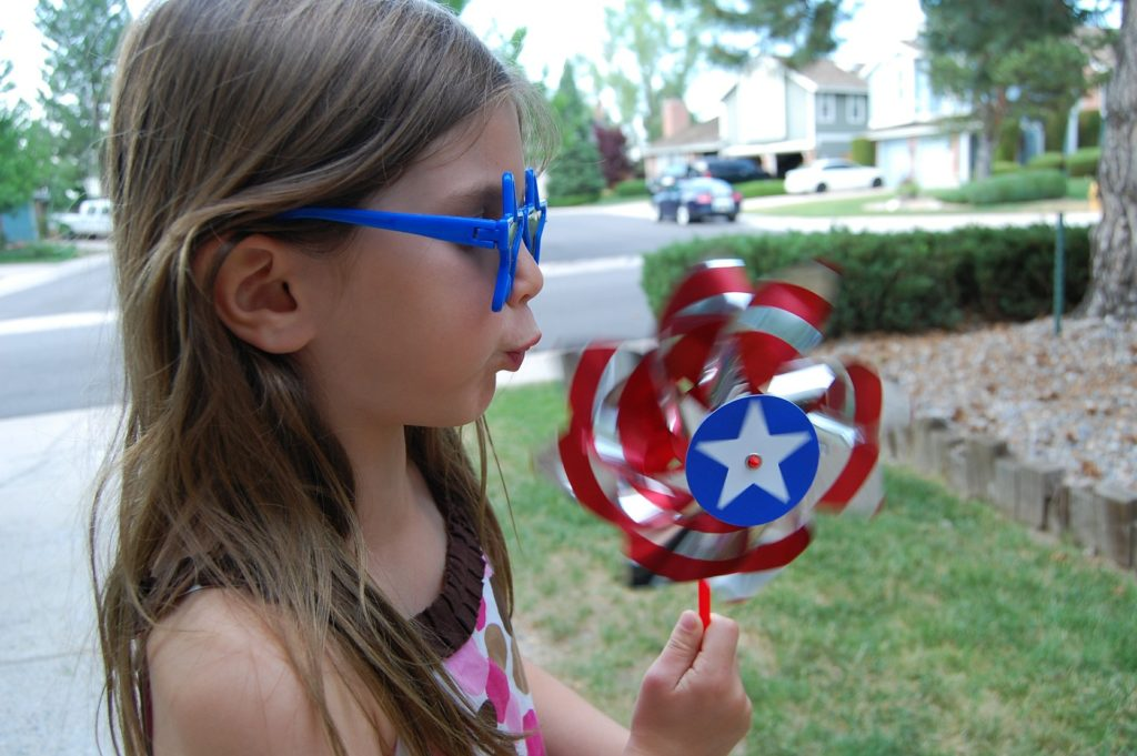 Girl blows pinwheel | calm down strategies for kids