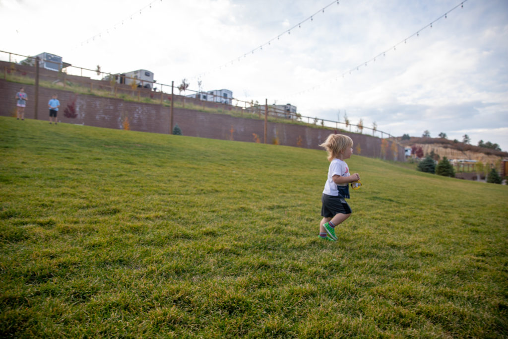 one year old boy runs in a large play area at the Jellystone Park Larkspur