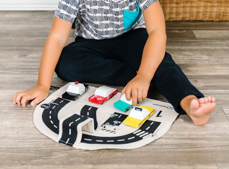 Car play mat for toddlers that can also be used for toy car storage