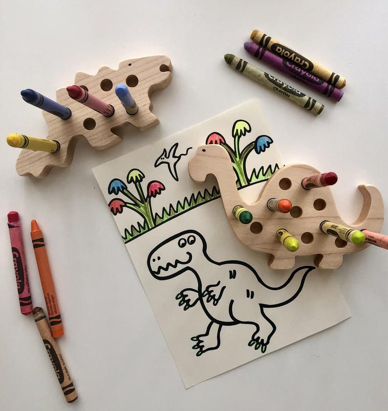Dinosaur crayon holder being used to stop crayons from rolling away