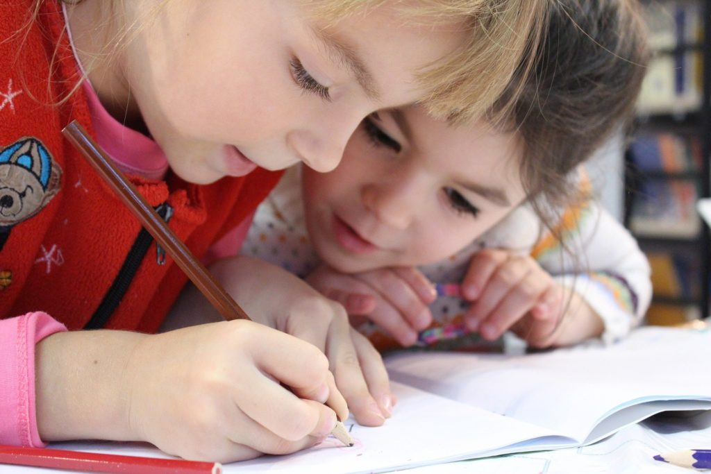 Two young kids coloring together in a coloring book | virtual thanksgiving ideas