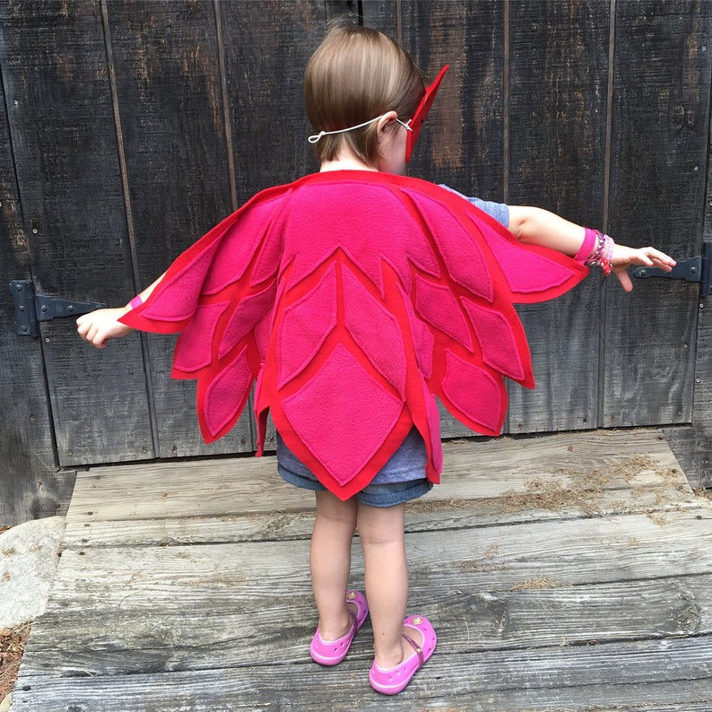 Toddler girl dressing up with owl wings